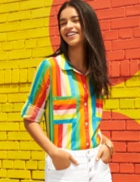 Rainbow striped top with white pants.
