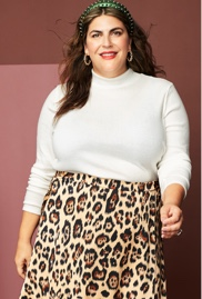 Katie Sturino wearing a plus size white sweater and leopard print skirt with green headband.