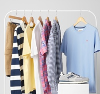 A white clothes rack featuring a variety of shirts, tees, shorts and trainers.