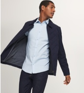 Black quilted jacket over a light blue shirt with indigo jeans.