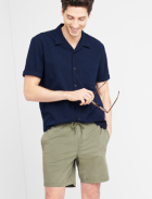 Men's clothes including a navy blue short sleeve collared shirt with olive shorts.