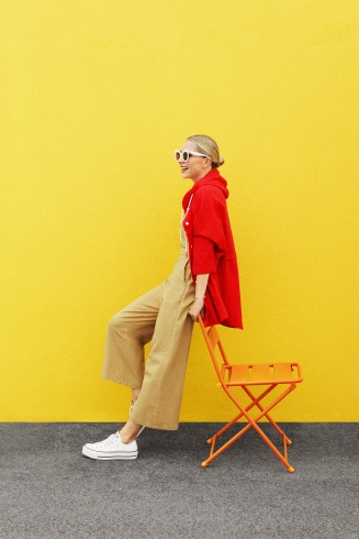 Women's outfit including tan Katie Sturino tan wide-leg overalls with red windbreaker jacket and white sneakers.