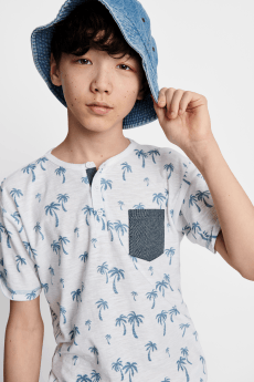 Kids clothes including a grey and blue palm tree print tee with grey pocket detail and a denim sun hat.