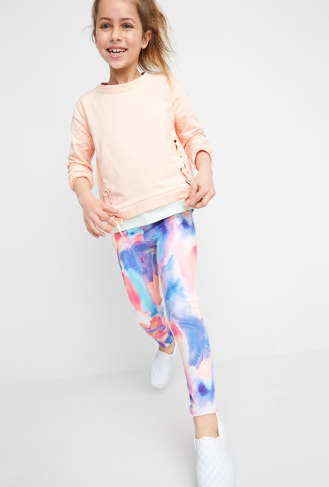 Pink shirt with blue and pink leggings with white sneakers