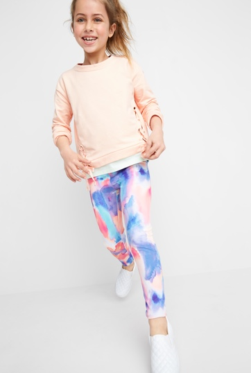 Pink shirt with blue and pink leggings with white sneakers.