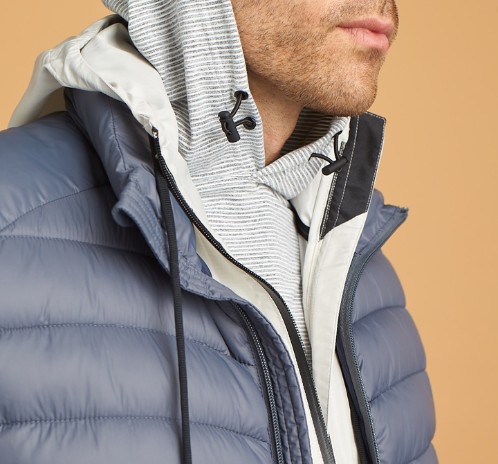 Grey and white hoodie with blue puffer jacket.