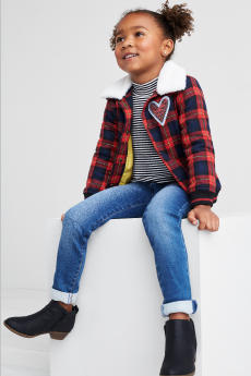 Kids clothes including a red plaid jacket with heart detail, jeans and black booties.
