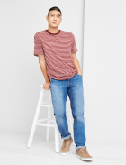 Men's clothes including a red and white striped tee, medium wash jeans and tan sneakers.