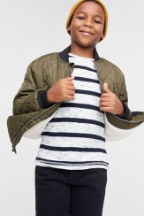 Stitch Fix Kids clothes including grey and black striped shirt, olive quilted jacket and black pants.