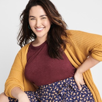 Stitch Fix women's clothes including a yellow sweater, maroon tee and blue floral print skirt.