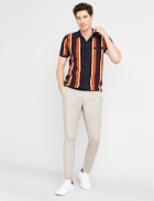 Men's clothes including orange and black striped collared tee with pocket detail and tan pants with shite sneakers.