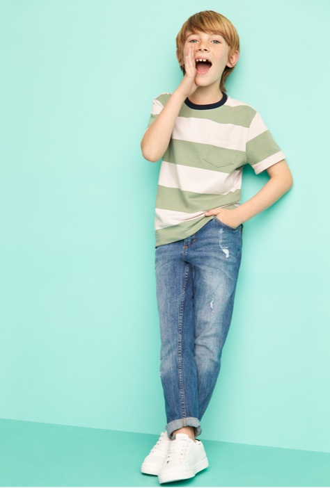 Green and white striped tee with jeans and white sneakers.
