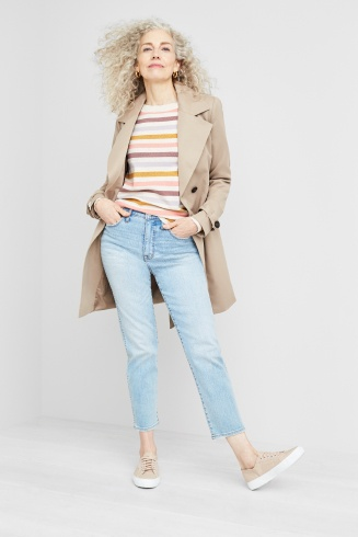 Outfit including a striped sweater, tan trench coat, jeans and tan sneakers.