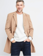 Long tan sport coat with white sweater and dark wash jeans.