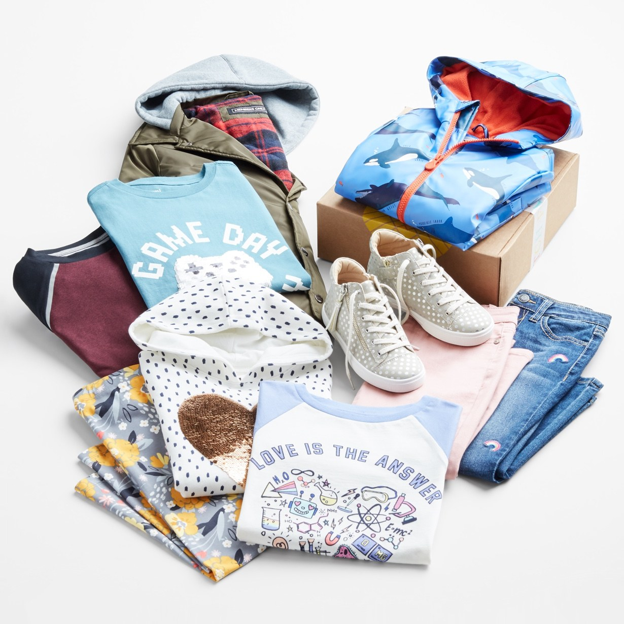 A pile of clothing including graphic tees, hoodie, jackets and sneakers.