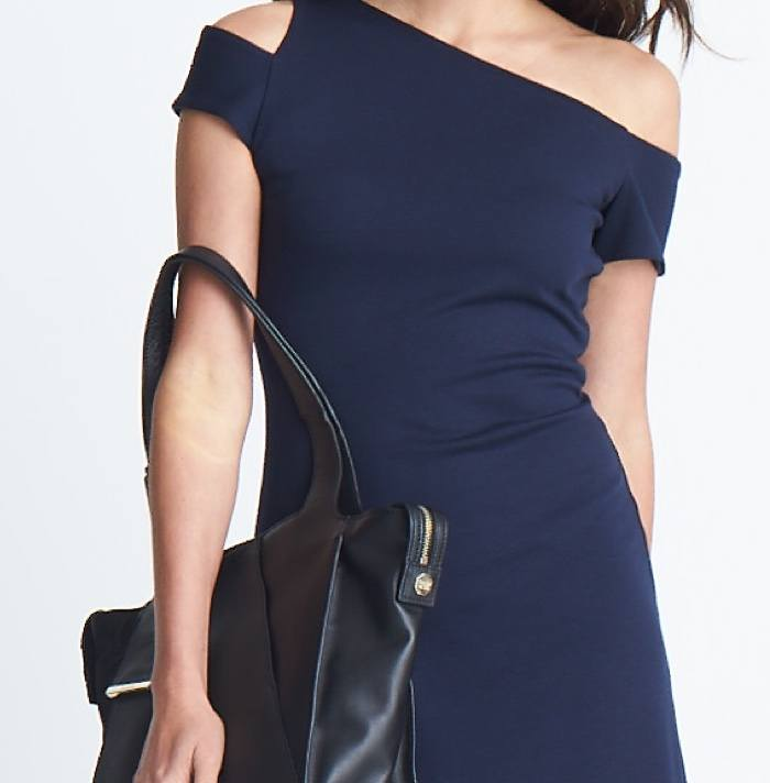 Navy blue off-the-shoulder sheath dress and black handbag.