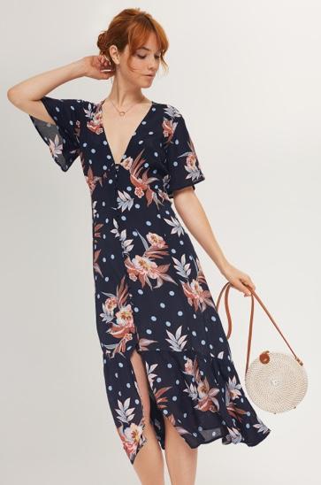Navy blue and floral v-neck dress and ivory circle cross body handbag.
