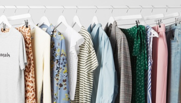 Close-up of a white clothes rack featuring a variety of men's and women's clothing.