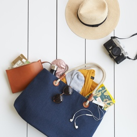 Straw hat, handbag and clutch purse with travel essentials.