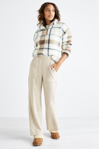 manbetx万博体育app 官方下载缝补妇女的衣服包括白色和棕色格子上衣与卡其裤和棕色鞋子。