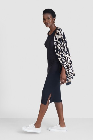 Stitch Fix women's clothes including a black dress and black and white print sweater with white sneakers.