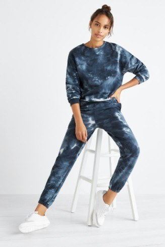 Stitch Fix women's athleisure clothing including blue tie-dye sweatshirt and jogger pants with white sneakers.