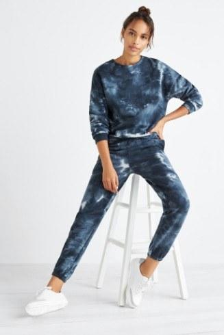 manbetx万博体育app 官方下载缝补妇女运动休闲服装包括蓝色扎染汗衫和慢跑裤与白色运动鞋。
