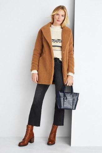 manbetx万博体育app 官方下载缝补妇女的衣服包括奶油毛衣,棕色短大衣,剪裁牛仔裤和棕色靴子与背部手提包。