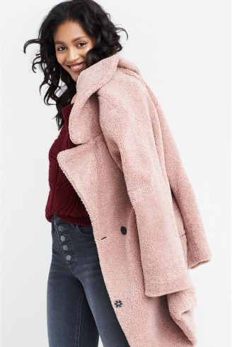 Stitch Fix women's clothes including maroon top, pink peacoat and grey jeans.