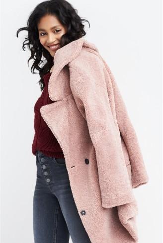 manbetx万博体育app 官方下载修复女士的衣服,包括栗色上衣,粉色大衣和灰色牛仔裤。