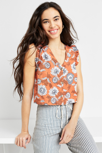 Stitch Fix women's outfit including an orange and grey floral V-neck sleeveless top with grey striped pants.