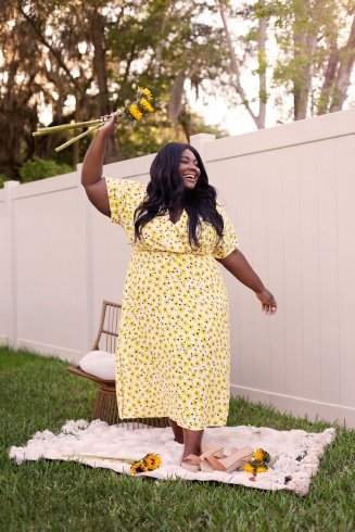 Katie Sturino yellow and white floral V-neck plus-size dress with flutter sleeves.
