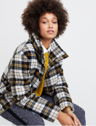 Yellow, black and white plaid jacket over yellow sweater with grey pants.